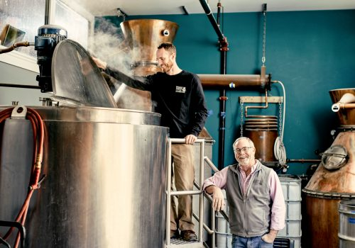 Dave and David Woods working in distillery in production room. Dave Jr looks into steaming cook kettle.